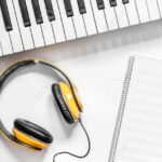 Headphone, notebook and synthesizer in music studio for dj or musician work on white desk background top view mock-up
